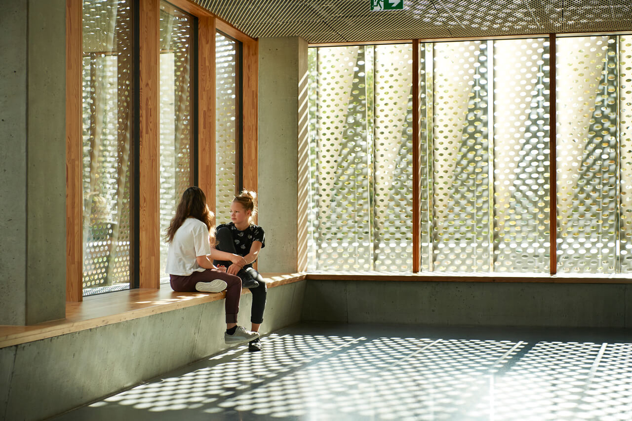 Two girls sitting in the school hall bathed in natural light