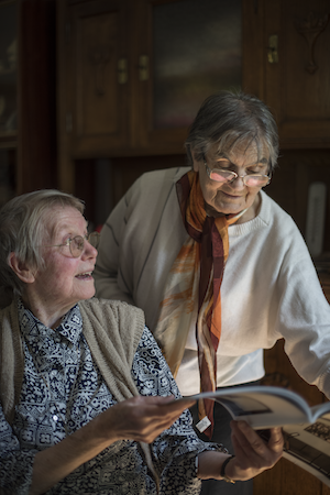 Two healthy elderly ladies discussing about a magazine